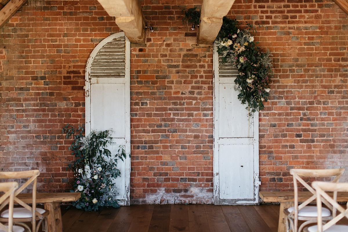 antique door and fresh flowers ceremony backdrop