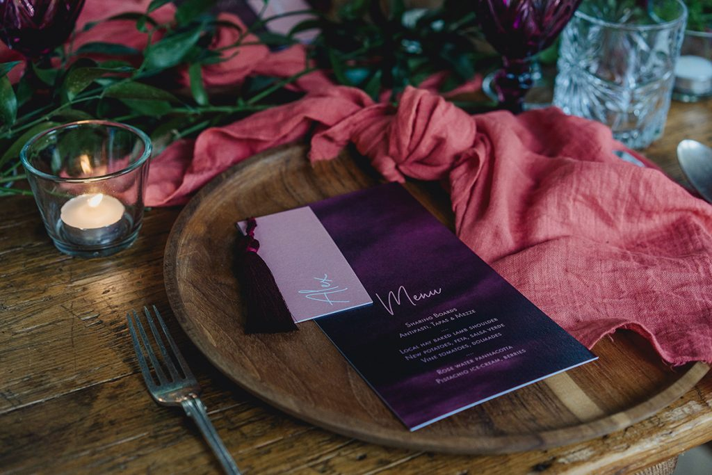 boho luxe wedding stationery by Knots & Kisses styled place setting with wooden chargers and linen fabric