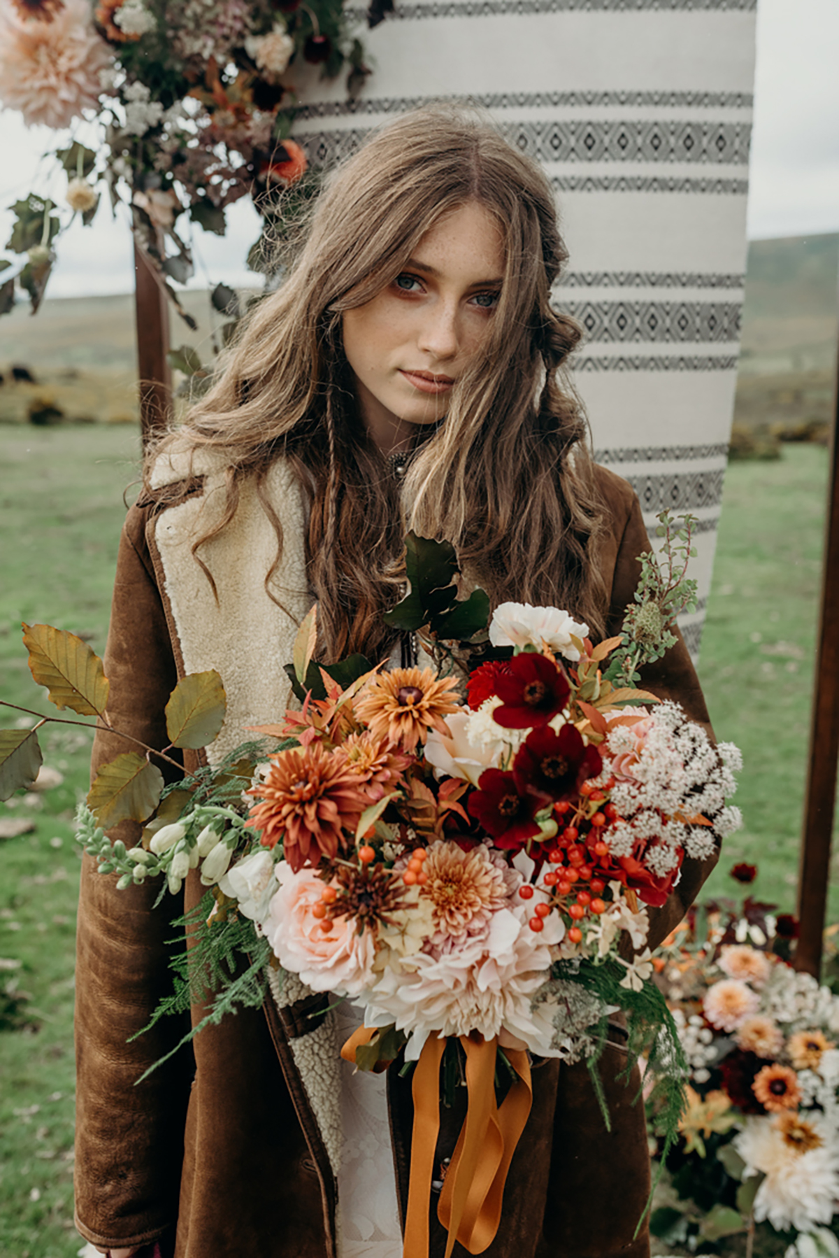 bride in shearling jacket with autumnal bouquet boho festival wedding inspiration