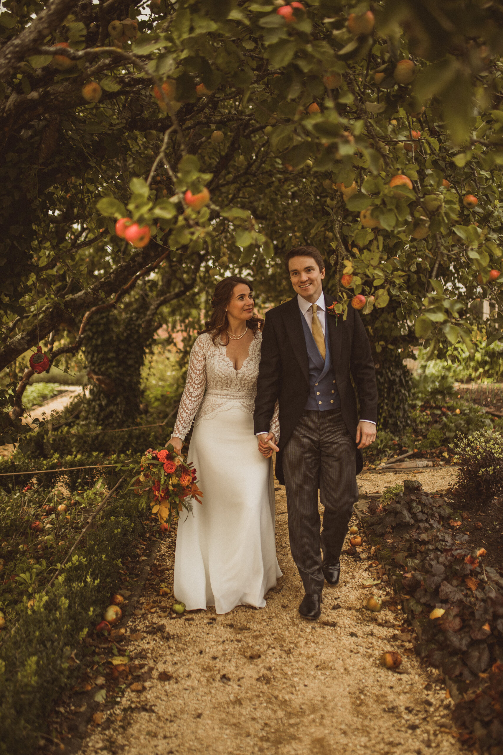 Cat and Fred's micro wedding Deer Park Country House bride and groom holding hands among apple trees