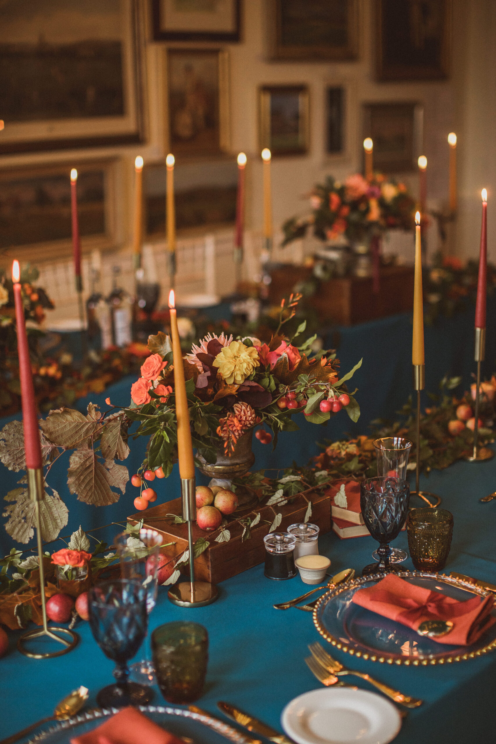 autumnal wedding tablescape in teal and orange with foliage and fresh fruit