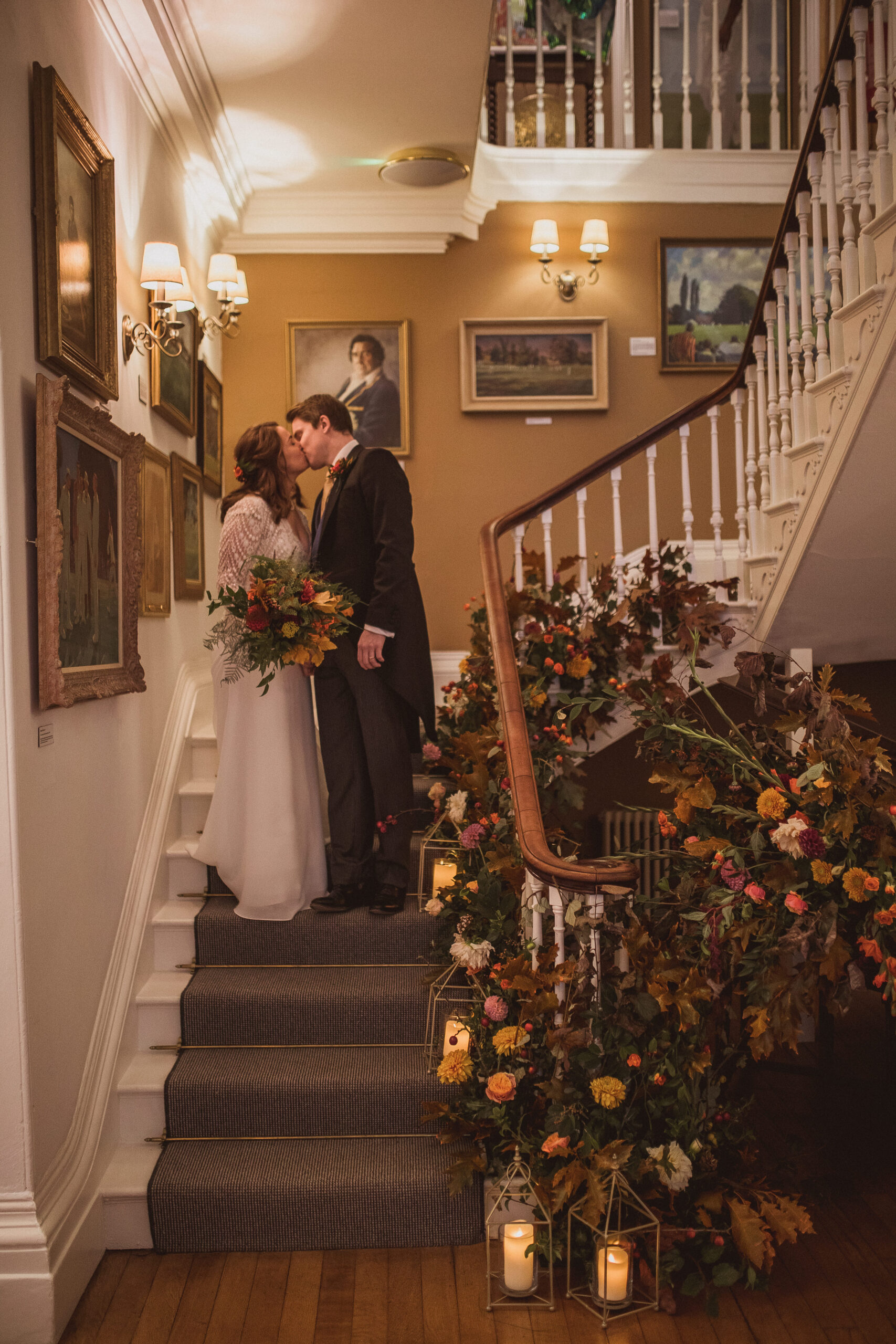 bride and groom kissing on staircase autumn wedding floral installation with lanterns