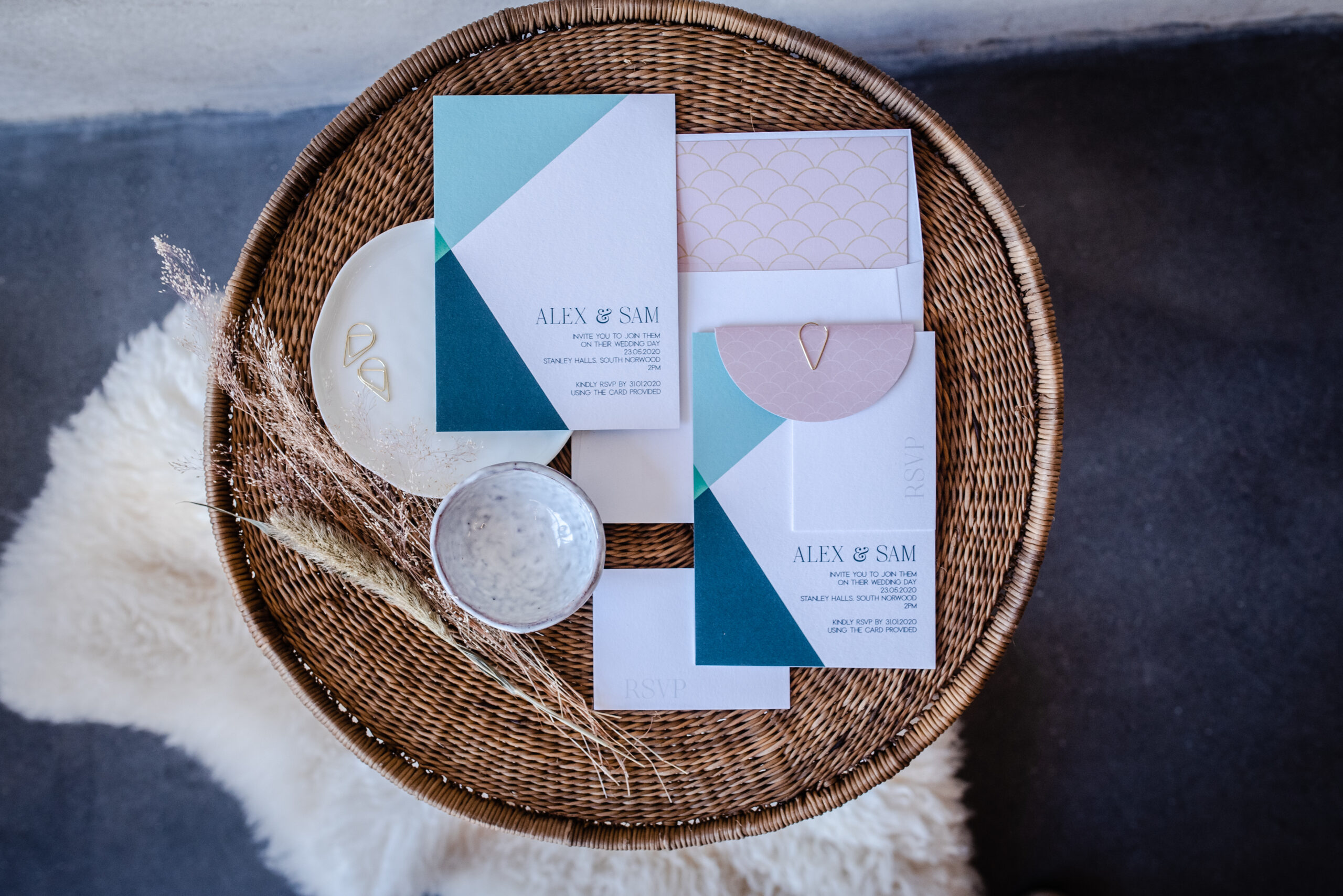 pastel wedding stationery abstract shapes flatlay on a rattan basket with dried flowers