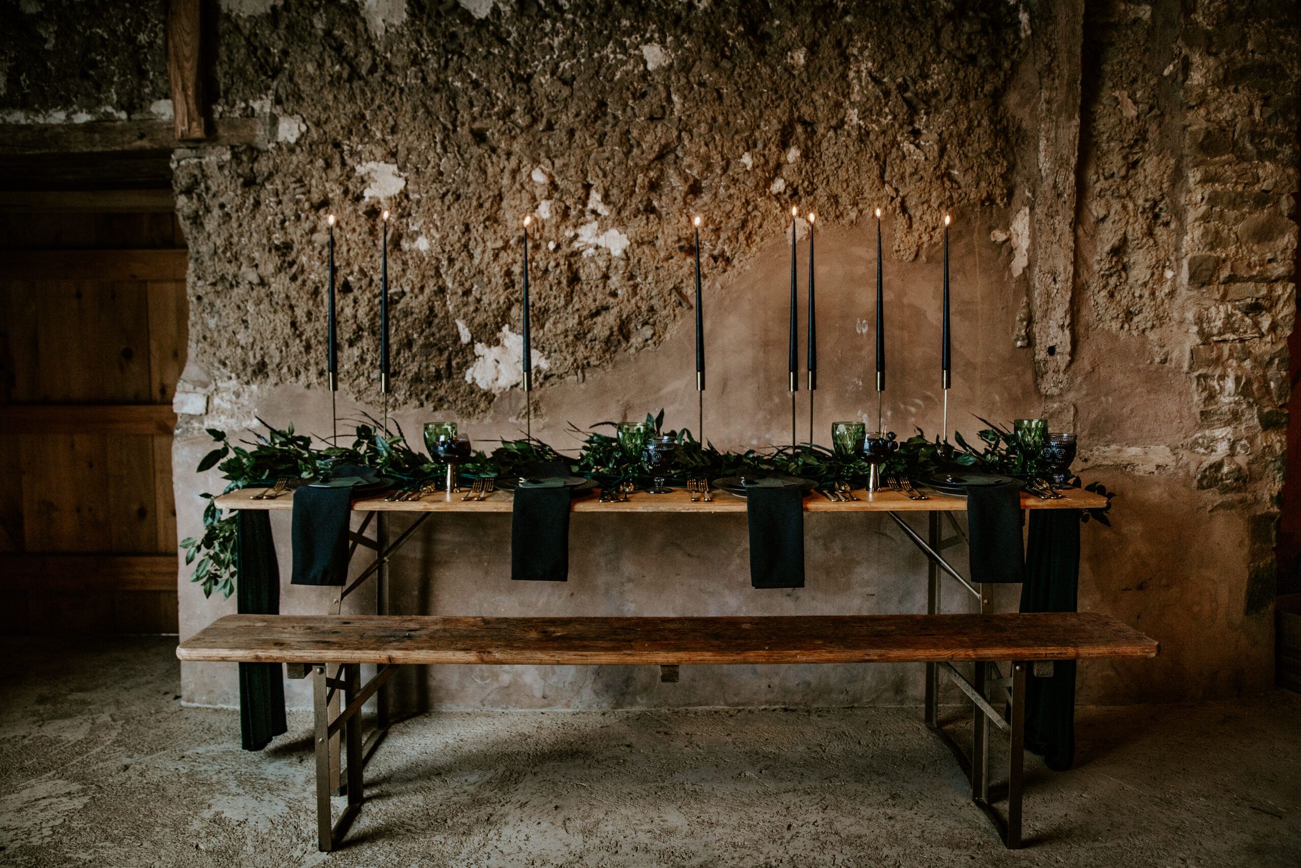rustic table and bench styled with black candles and greenery