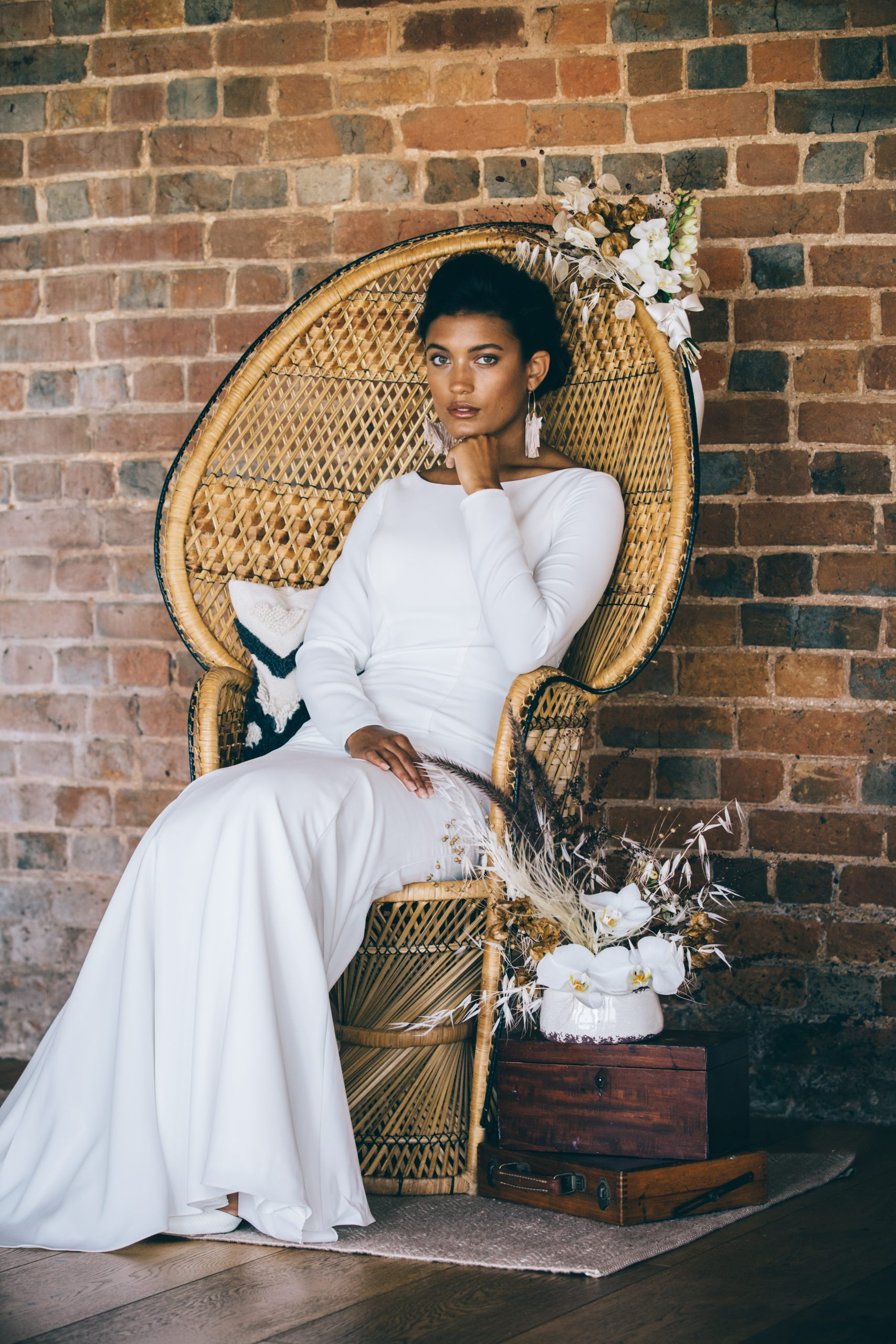 bride posing in peacock chair boho luxe wedding styled shoot