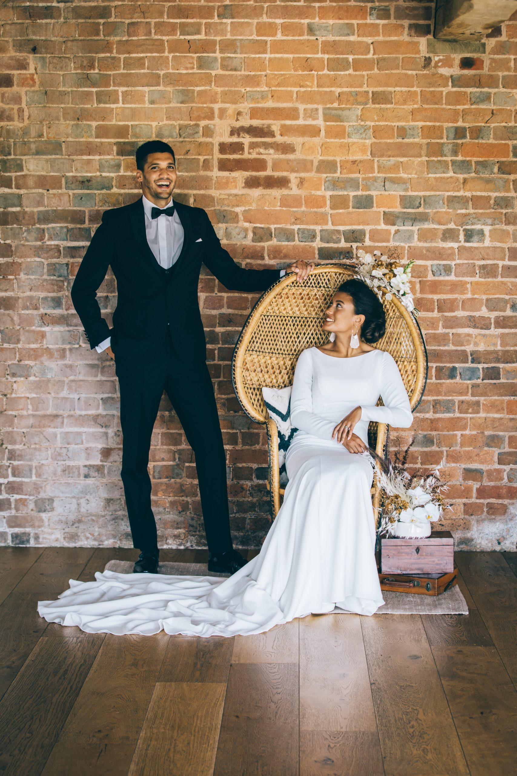 boho luxue styled wedding shoot bride and groom posing beside peacock chair
