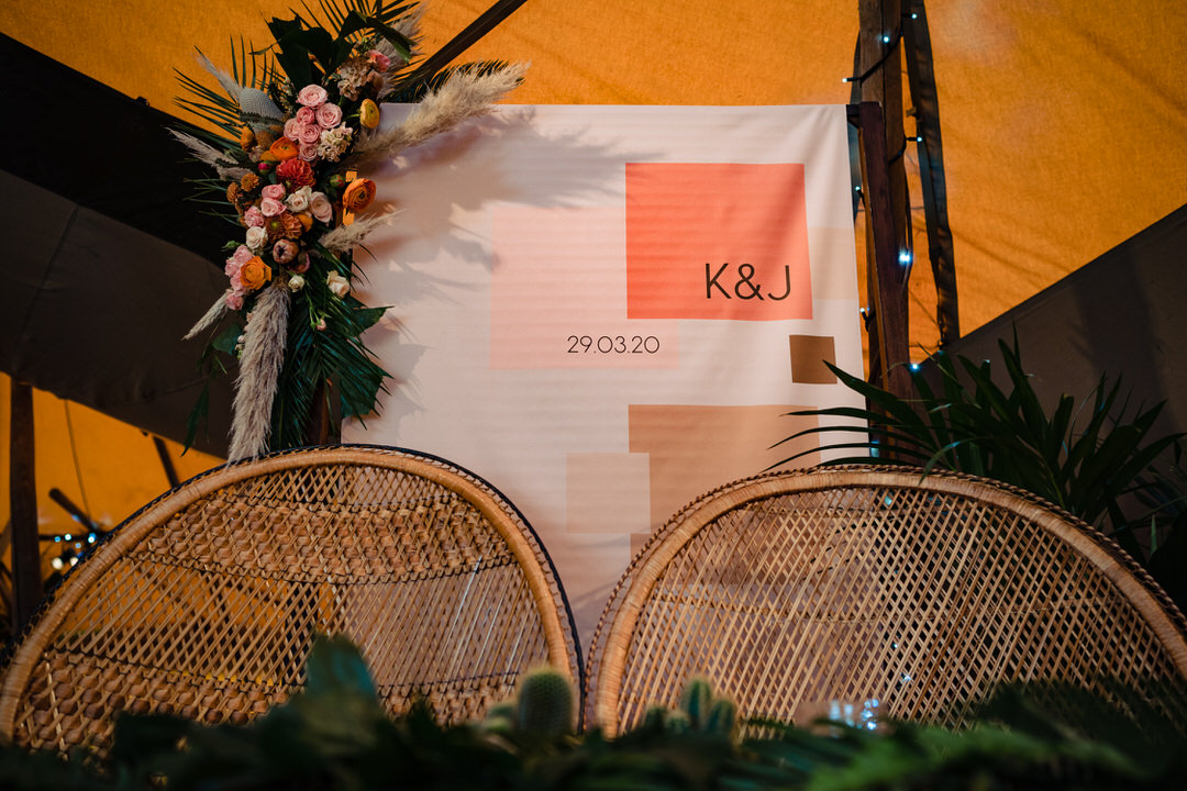 linen wedding ceremony backdrop with dried flowers pampas grass peacock chairs