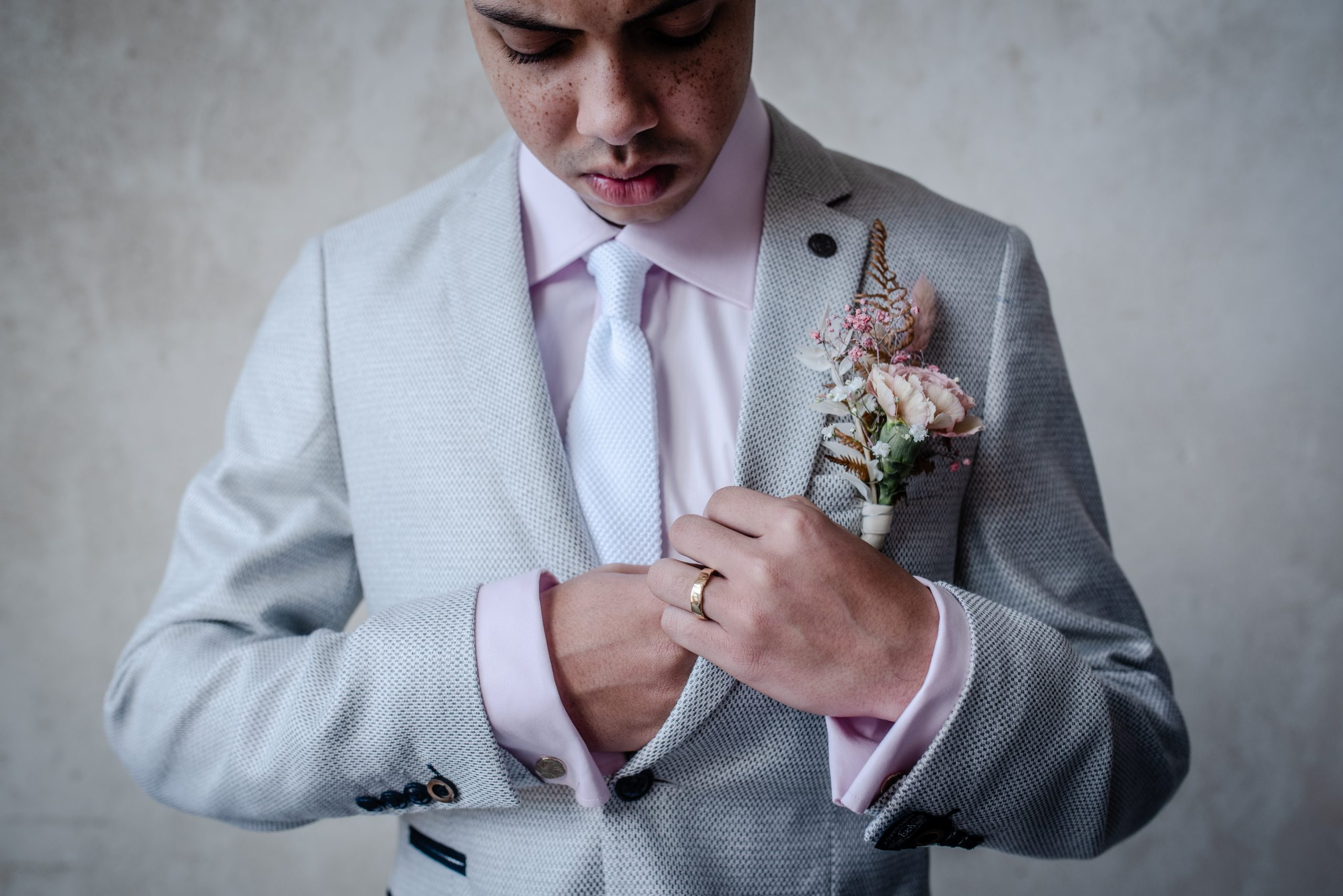 Groom in pale blue suit with pastel pink buttonhole
