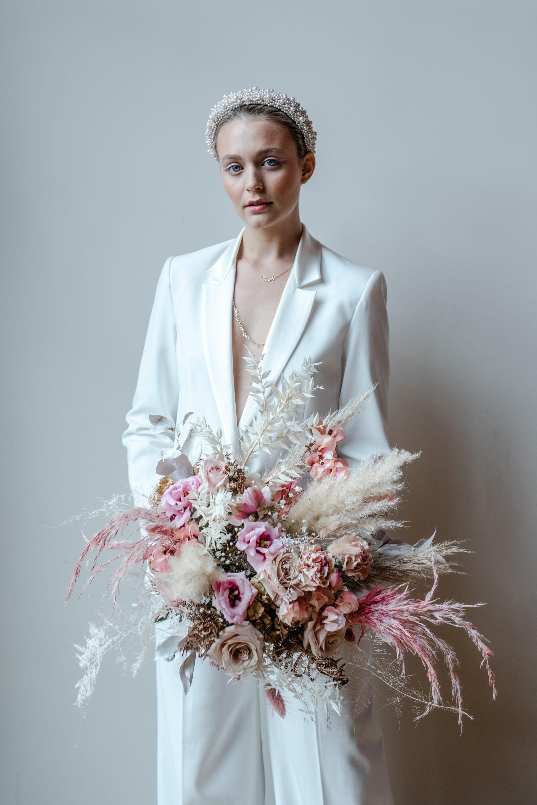 Modern bride in white trouser suit with pearl headband and large pastel pink bouquet